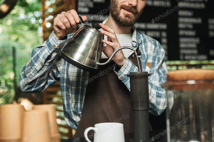 Portrait of happy barista man making coffee while working in str