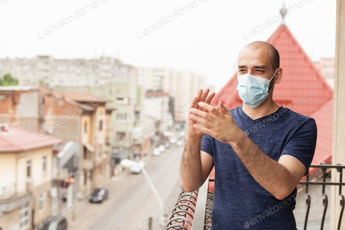 Adult man with protection mask clapping