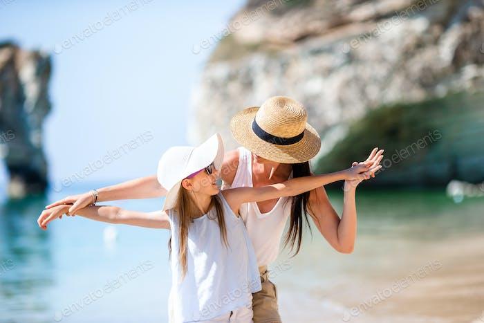 Schöne Mutter und Tochter am Strand genießen Sommerurlaub