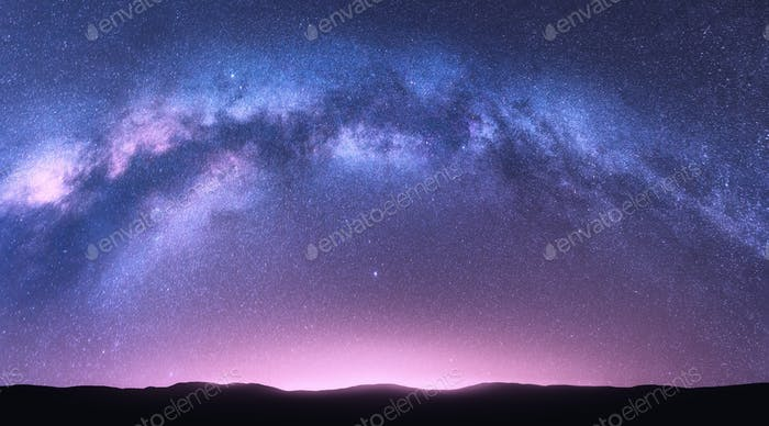 Milky Way arch. Night landscape with bright arched milky way