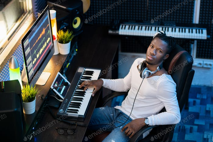 Young Afroamerican man in casualwear looking at you while sitting in studio