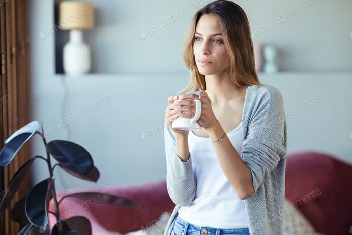 Beautiful young woman standing near the window while drinking coffee in the living room at home.