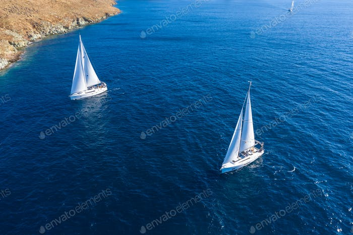 Sailing boats with white sails, rippled sea background