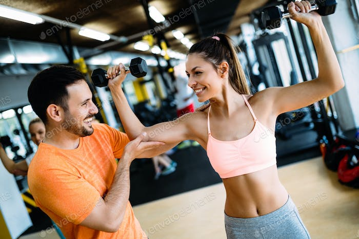 Personal trainer instructing trainee