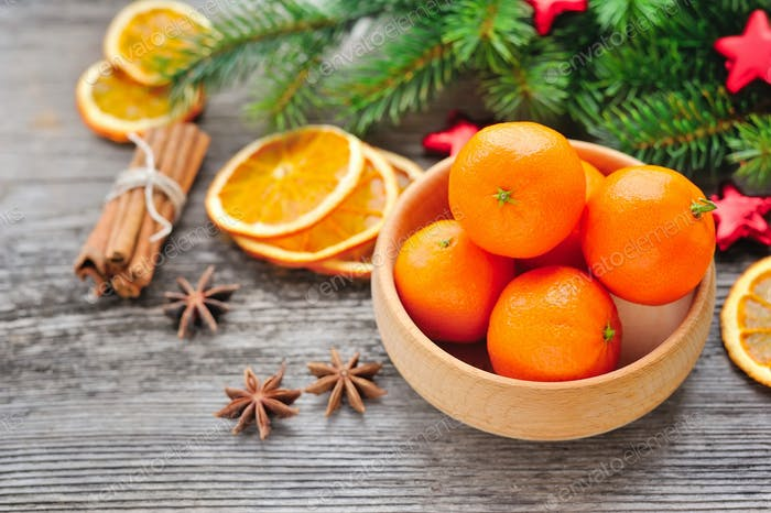 Tangerines and Christmas tree branches on a wooden table. Natura