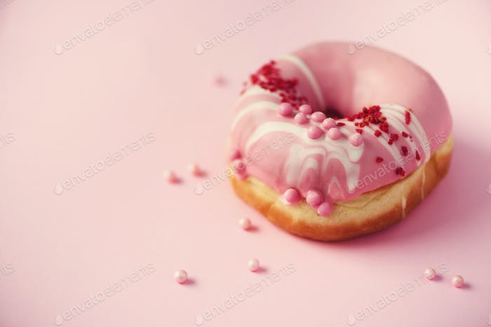 Sweet doughnut with pink icing on pastel background. Tasty donut on pink texture, copy space, top