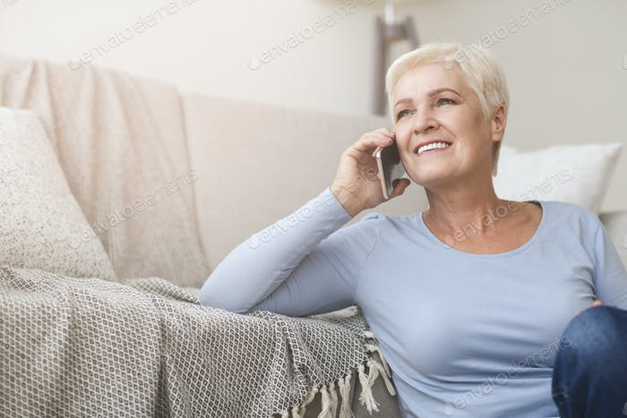 Happy female pensioner talking by phone at home