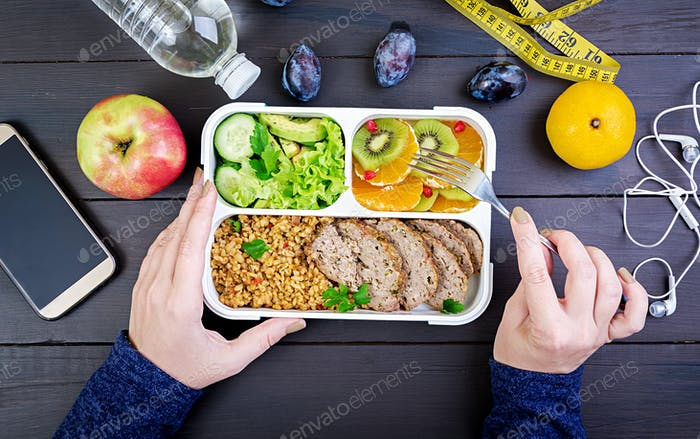 Top view showing hands eating healthy lunch with bulgur, meat and fresh vegetables