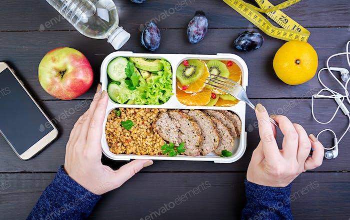 Draufsicht zeigt Hände essen gesundes Mittagessen mit Bulgur, Fleisch und frischem Gemüse
