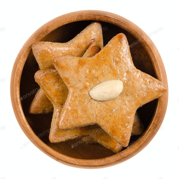 Gingerbread stars in wooden bowl over white