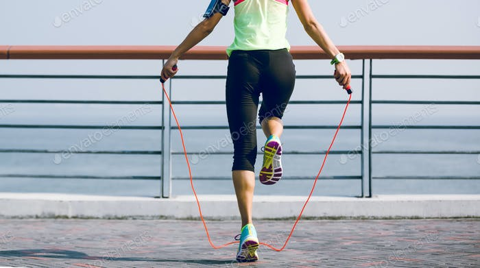Fitness woman jumping rope on seaside