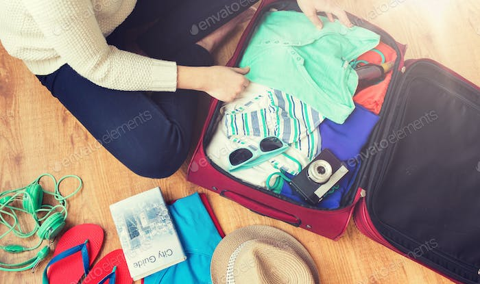 close up of woman packing travel bag for vacation