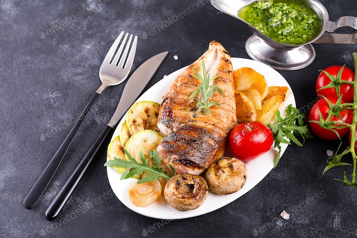 Grilled chicken breast on a plate with tomatoes, mushrooms and green sauce on a stone background