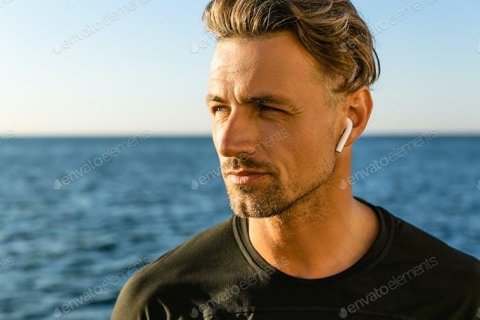 close-up portrait of handsome adult man with wireless earphones on seashore looking away