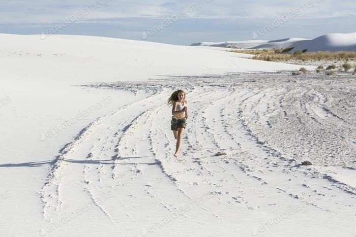 A teenage girl running in the sand, White Sands Nat'l Monument, NM