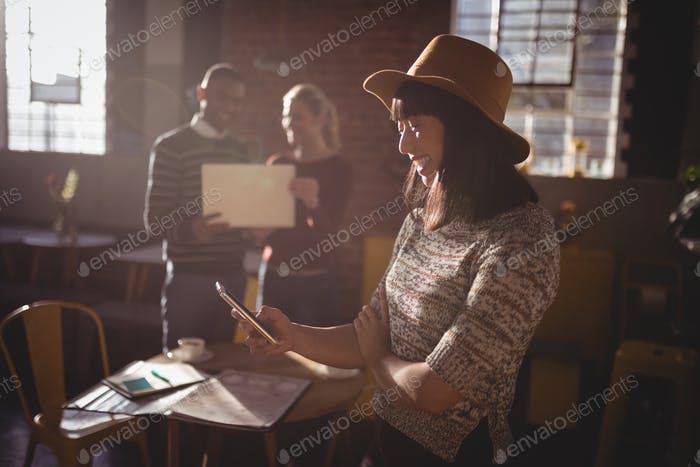Smiling woman using smartphone against colleauges