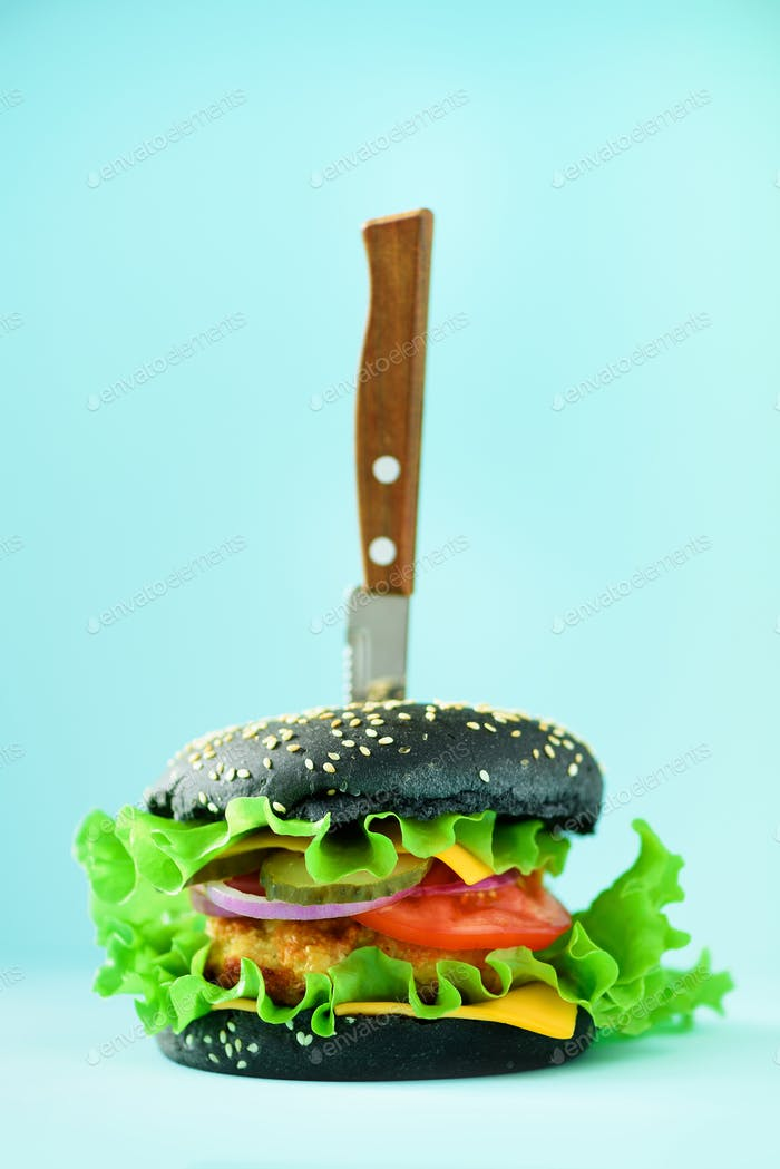 Fast food concept. Juicy black burger with knife on blue background. Take away meal. Unhealthy diet