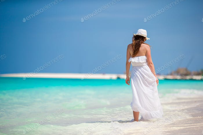 Young beautiful woman during tropical beach vacation. Enjoy summer vacation alone on the beach with