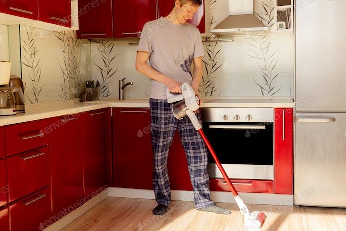 Hombre limpieza casa con aspiradora inalámbrica.