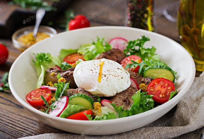 Warmer Salat aus Hühnerleber, Rettich, Gurken, Tomaten und Ei pochiert. Gesundes Essen. Diät-Menü