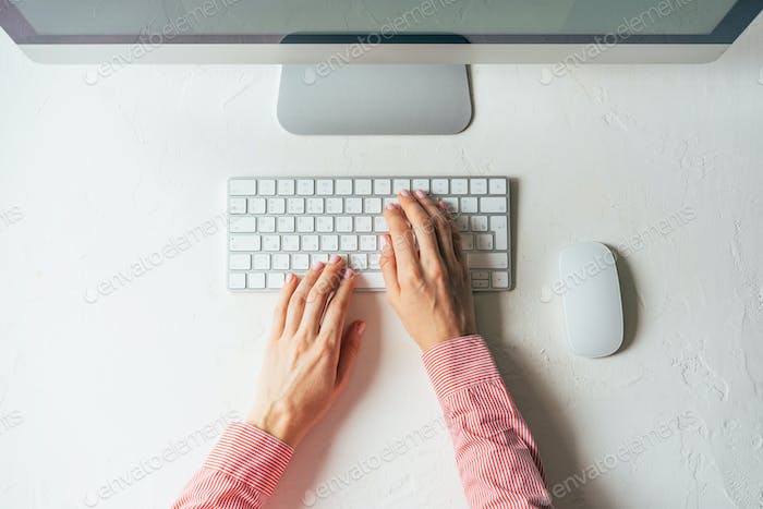 Layout of a minimalistic workplace with a computer. Female elegant hands are typing on the keyboard.