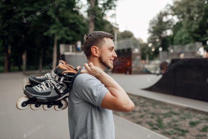Roller skating, skater carries skates on shoulder