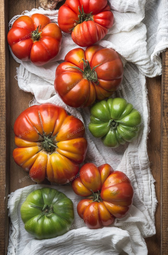 Colorful Heirloom tomatoes on white textile in rustic wooden tray, top view