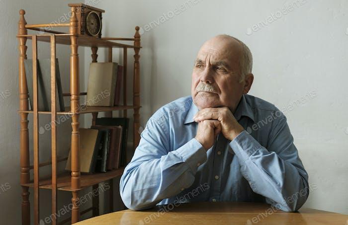 Älterer Mann sitzend an einem Tisch denken