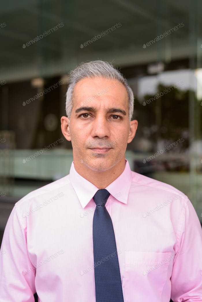 Face of handsome Persian businessman with gray hair outside modern building