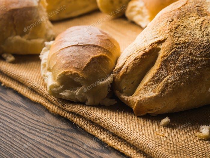 Frisch gebackenes Brot auf Sackleinen dunklem Holzhintergrund