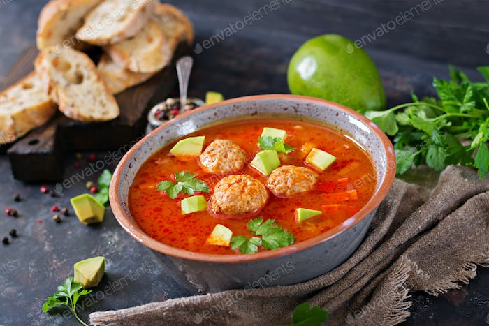 Spicy tomato soup with meatballs and vegetables. Served with avocado and parsley. Healthy dinner