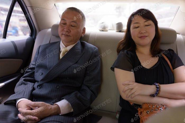 Mature Asian businessman and mature Asian woman sleeping inside car together