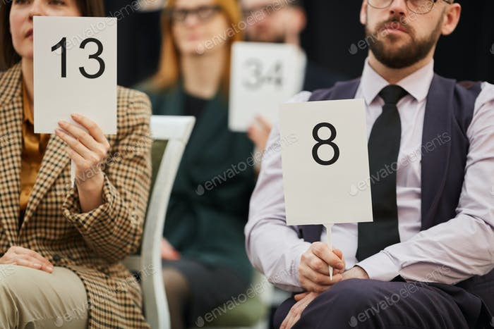 Business people sitting at auction