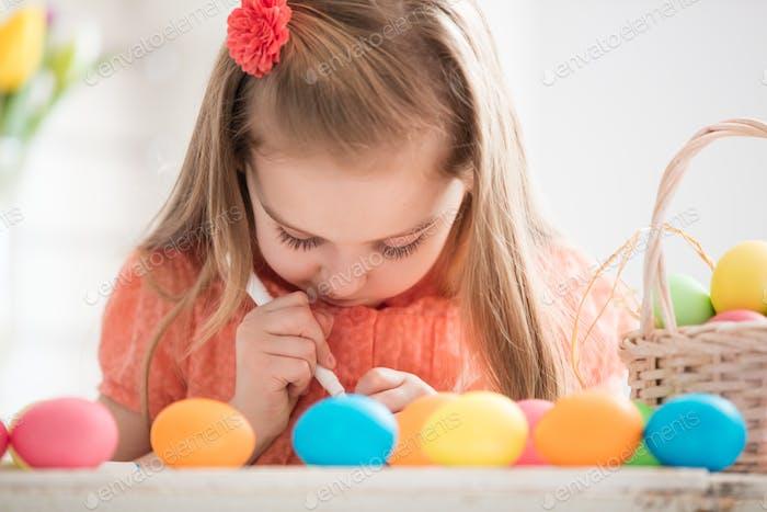 Fokussierte Kind Erstellen von Zeichnungen auf bunten gefärbten Eiern