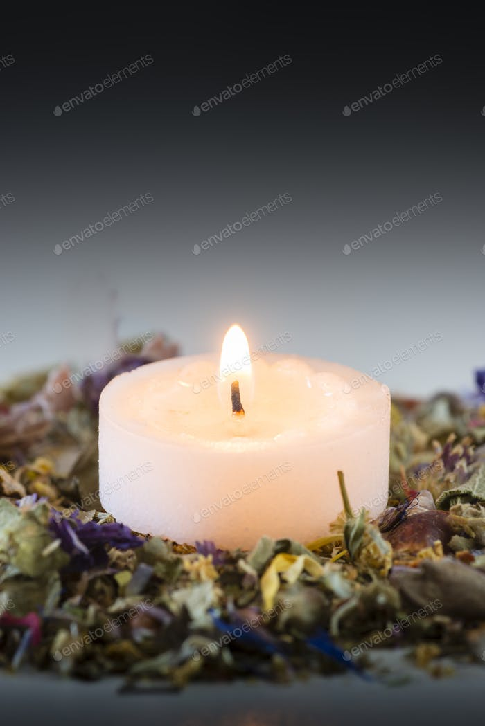 Flower potpourri  with lit candle.
