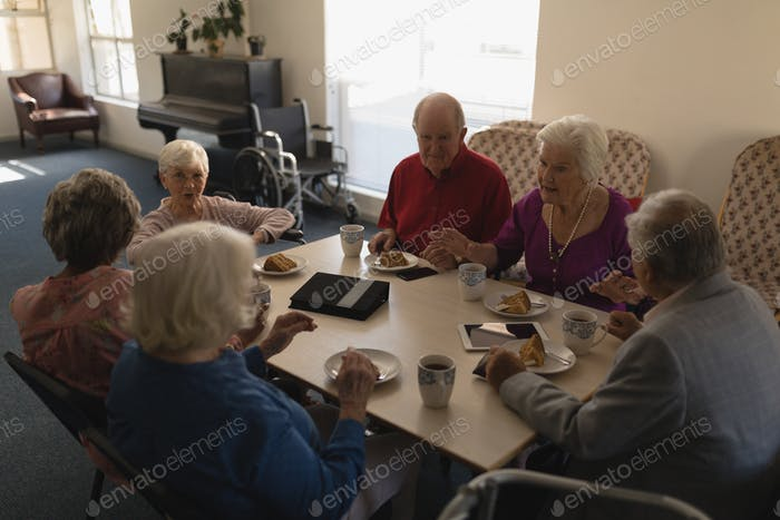 High angle view of group of senior friends having breakfast on dining table at home