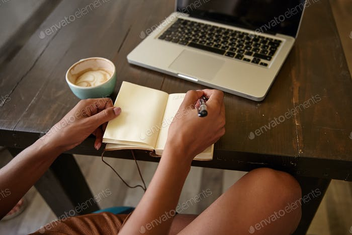 Indoor close-up of wooden countertop with laptop on it, freelancer female working in public place