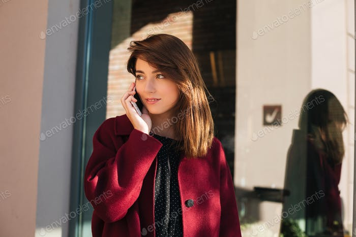 Young lady in coat standing on street and dreamily looking aside while talking on her cellphone