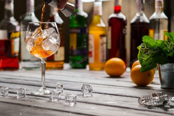 Jigger pours liquid in wineglass