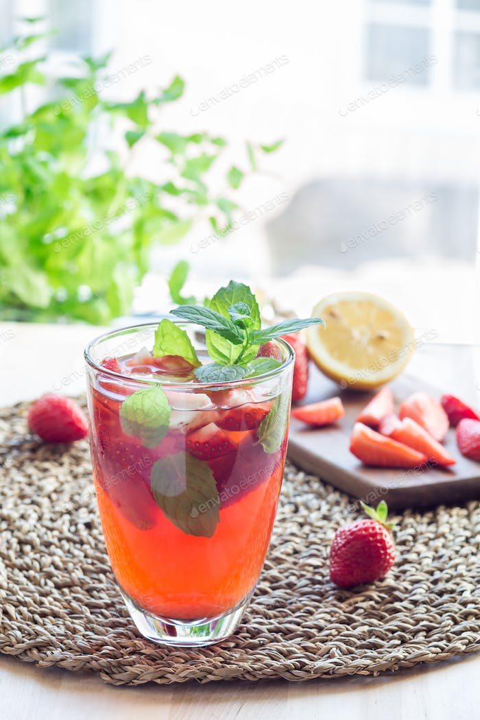 Glass of refreshing iced tea with strawberries and mint, vertica