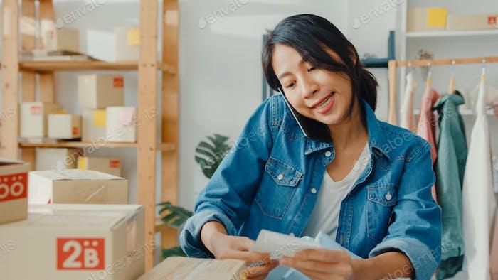 Mujer de negocios asiática utilizando teléfono inteligente llamada recepción orden de compra en la oficina en casa.
