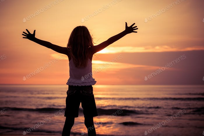 Happy little girl  standing on the beach