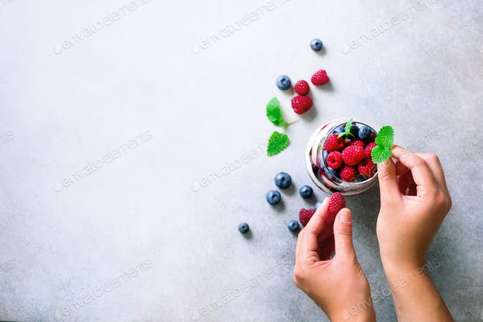 Woman hands decorating delicious dessert, chia pudding. Copy space, top view