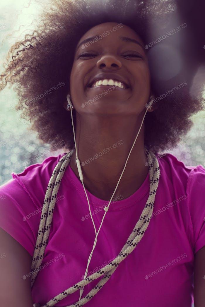 Porträt der jungen afro amerikanische Frau in der Turnhalle beim Hören mus