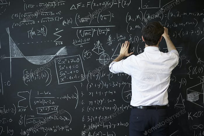 Young man writing on blackboard