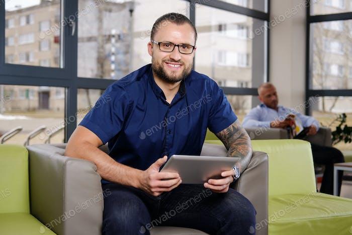 Geschäftsmann in einem blauen Hemd sitzt auf der Couch im Büro gekleidet