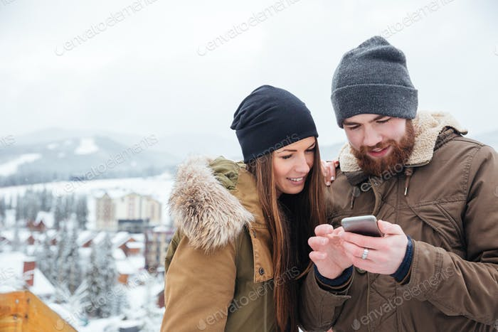 Happy couple using smartphone together in winter
