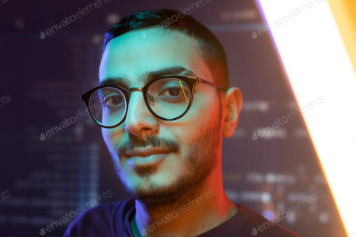 Face of young clever confident programmer or software developer in eyeglasses