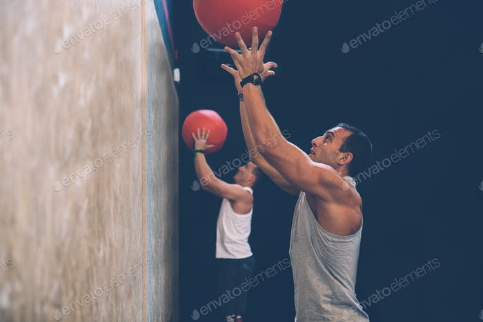 Sporty men doing wall ball exercise