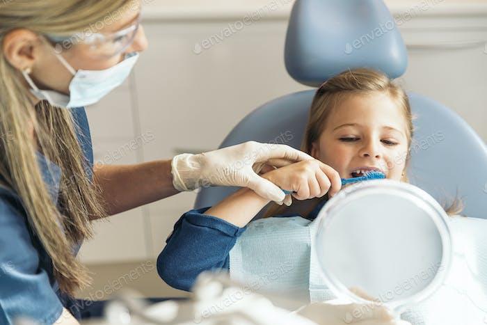 Arzt Zahnarzt lehrt ein Kind Zähne zu putzen